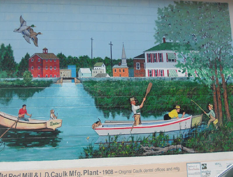 Mural depicting skiffs on the water in fornt of a downtown scene