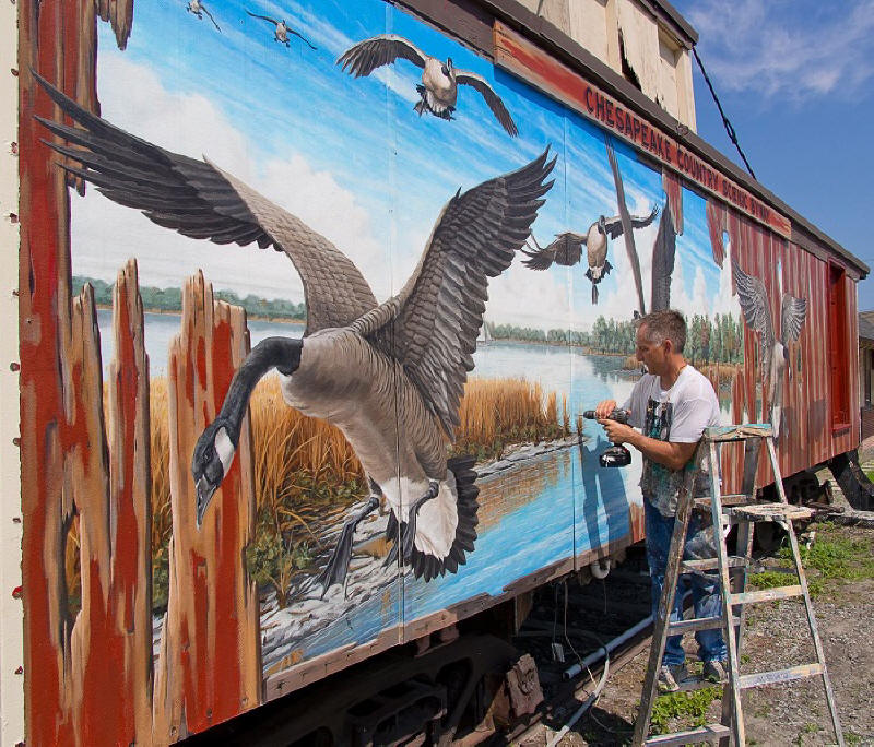Mural side of J. M. Clayton Seafood, overlooking Cambridge Creek, portrays The Watermen, a great blue heron,
