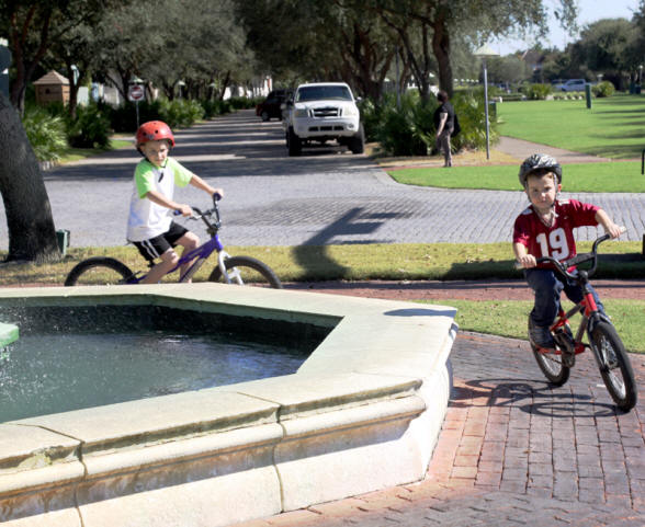 Two little boys riding bikes at fountain in Rosemary Beach, florida