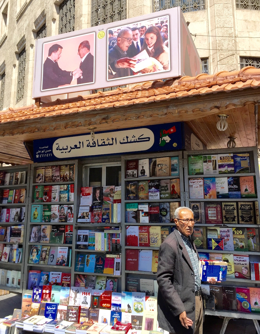 street bookstore in Amman with owner in front. Picture of King and Queen shoping there above