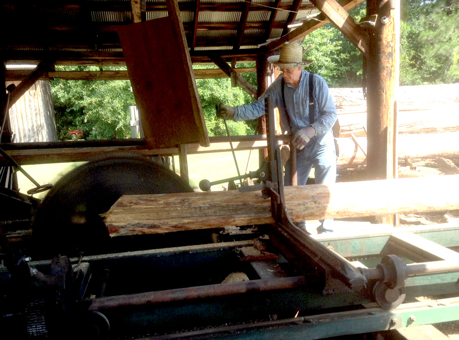 Docent cutting timber at the sawmill at georgia agrirama