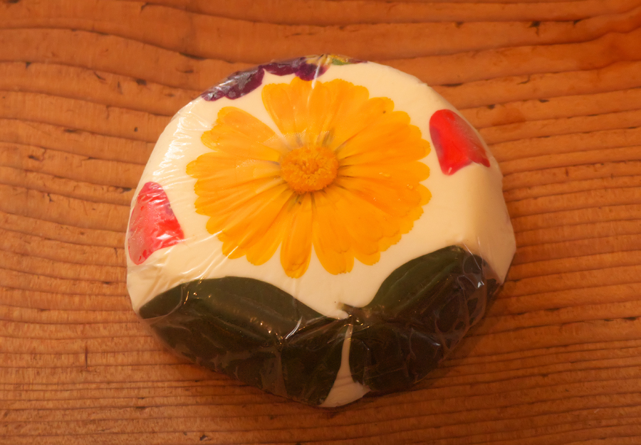 Cheese decorated with yellow edible flower, red petals and green herb leaves