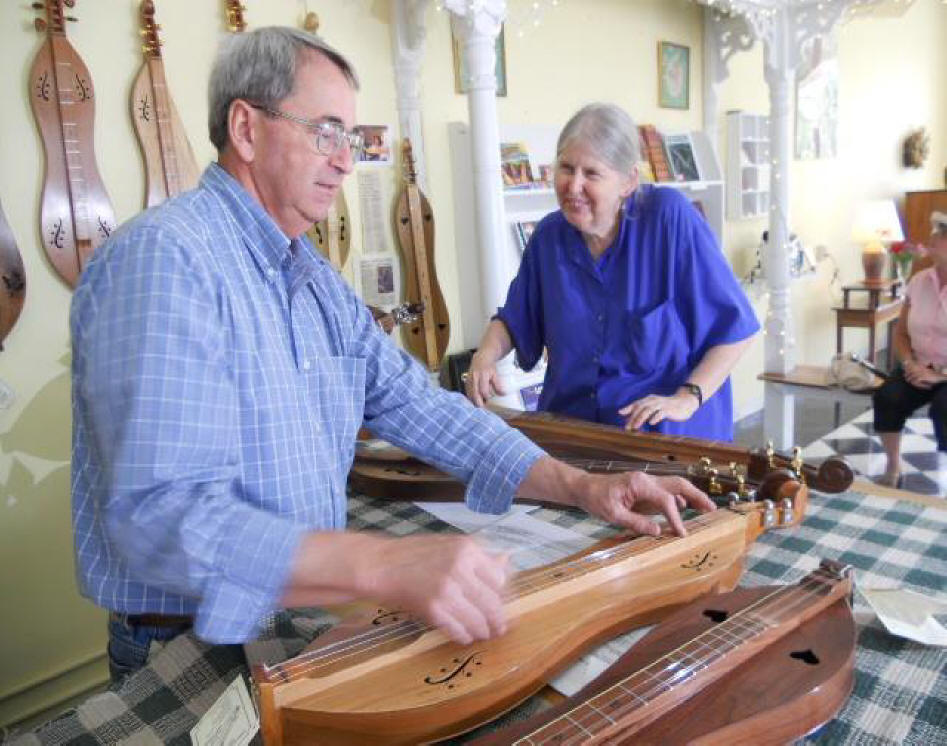 Dulcimer maker Warren May and a friend strum up a tune on three dulcimers in May's shop.