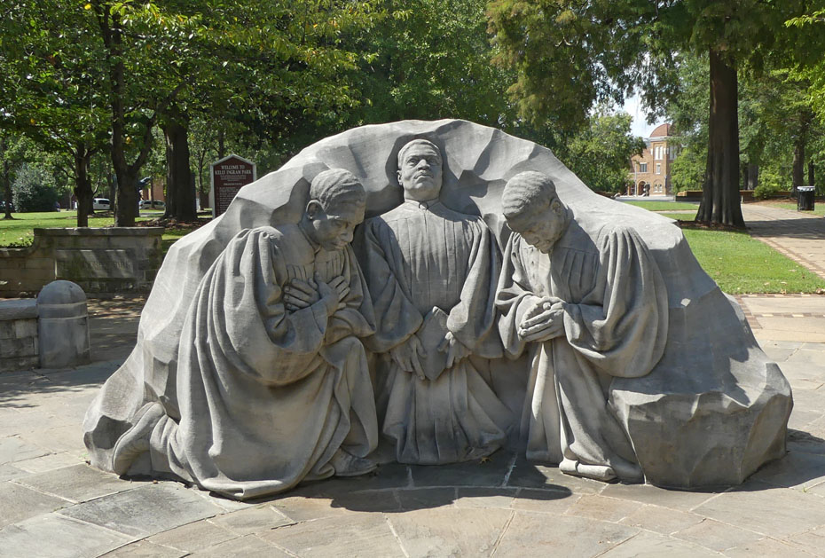 Sculpture in Kelly Ingram P{ark showing 3  preachers praying