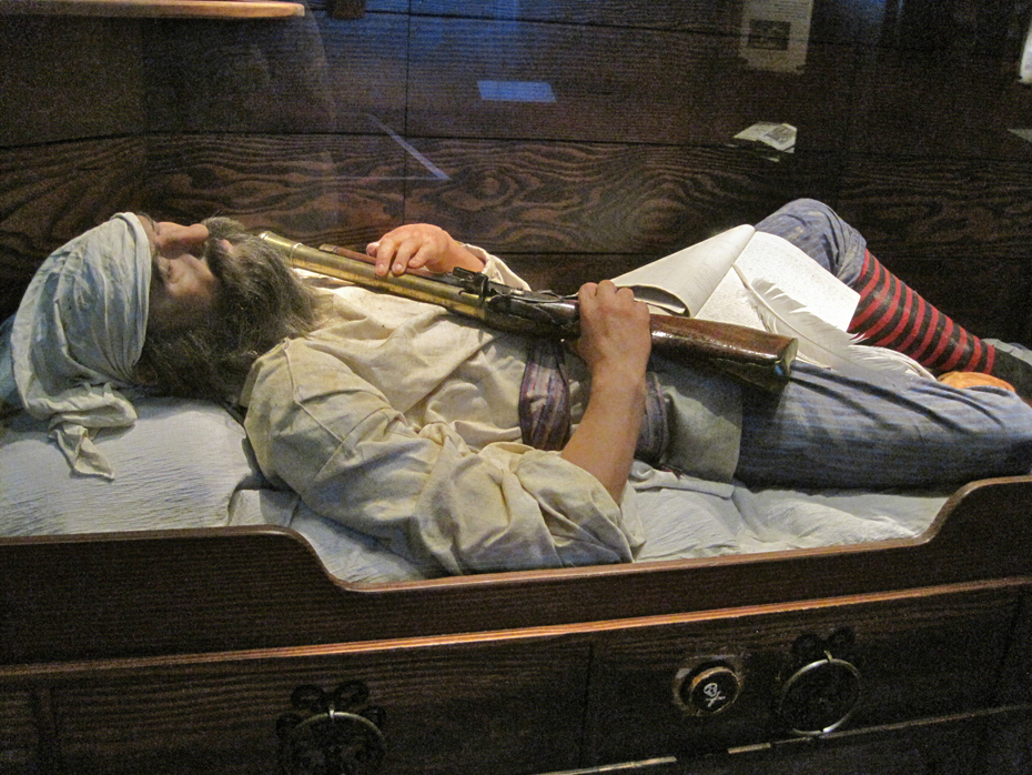 ":pirate"" sleeps in hsi bunk with musket at the St. Augustine Pirate and Treasure Museum"