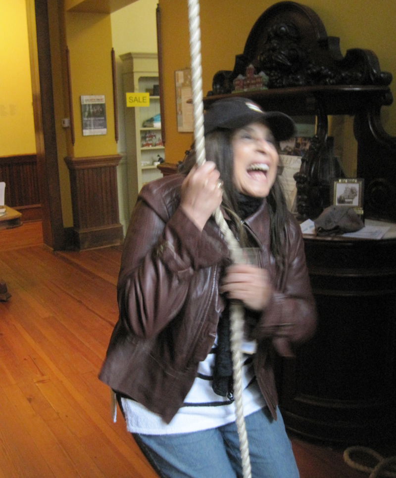 Woman ringing bell at former schoolhouse in Madison