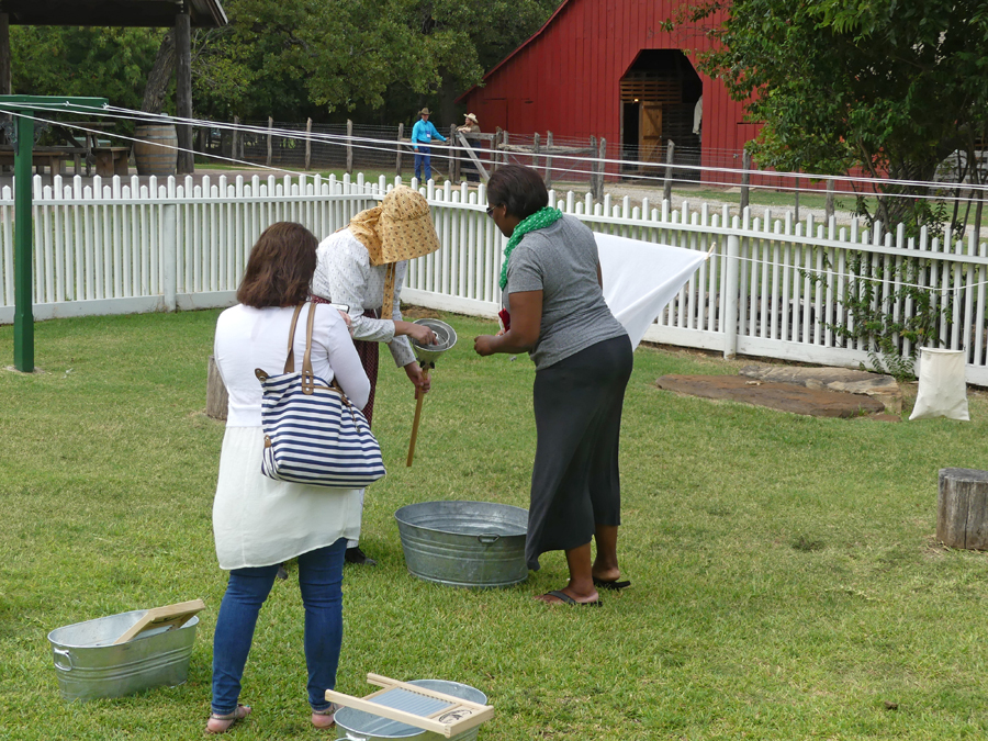 a docent shows two journalists how washing was done at Nash Farm