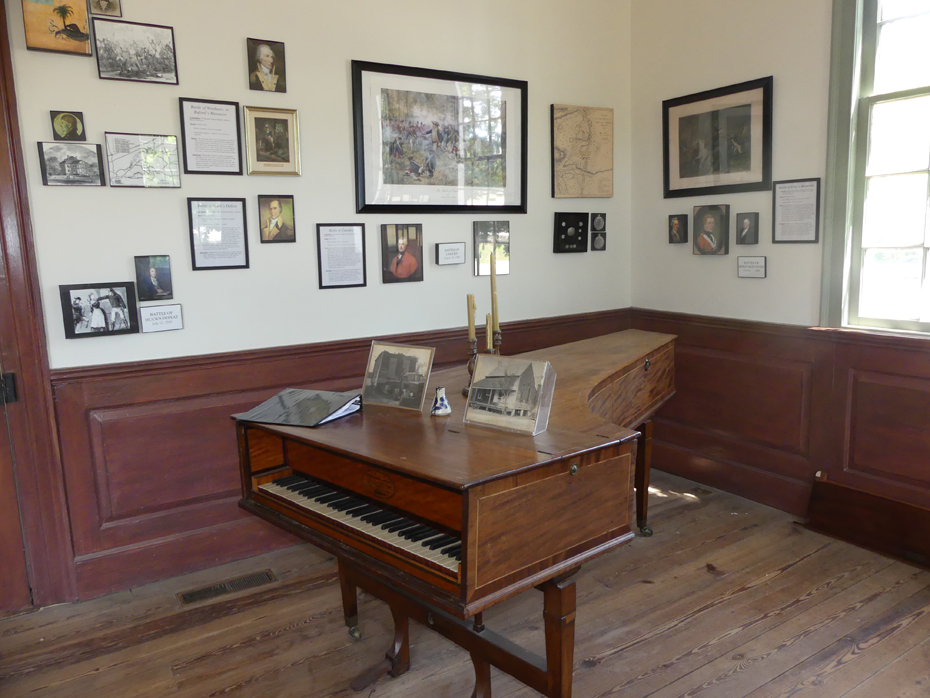Interior of John Craven house showing piano and pictures on wall at Historic Camden