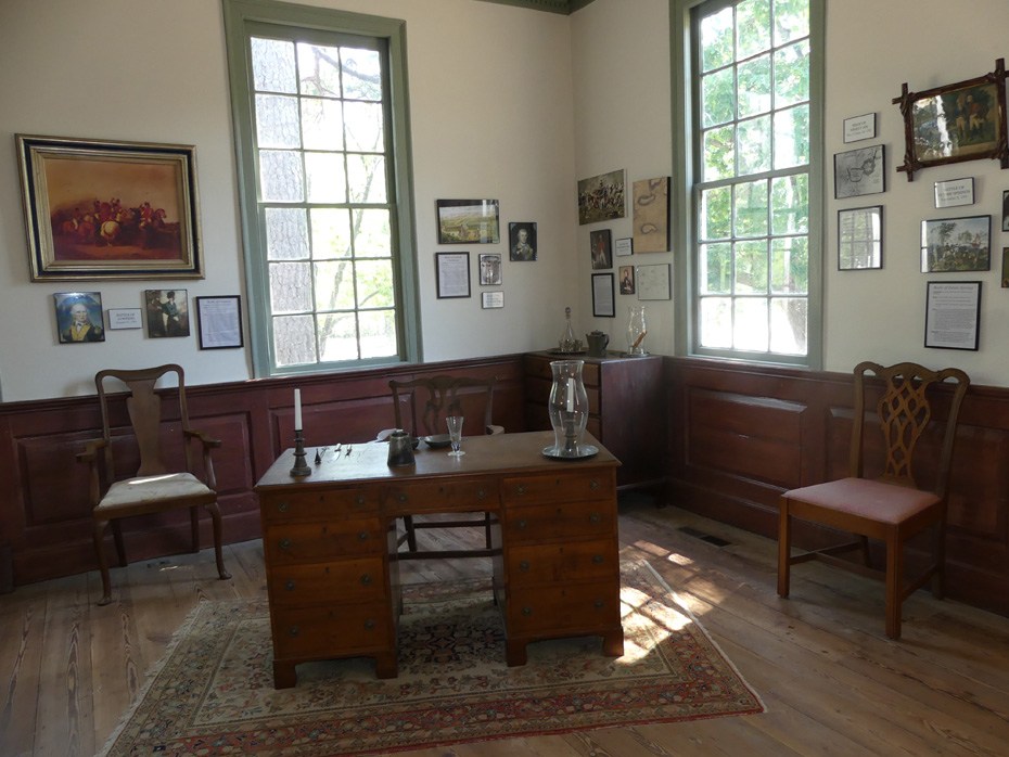 Interior of John Craven house showing desk and pictures on wall at Historic Camden