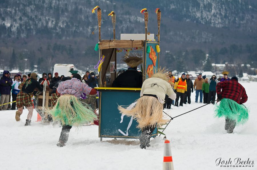 outhouse race with team wearing hula skirts at Lake George carnival