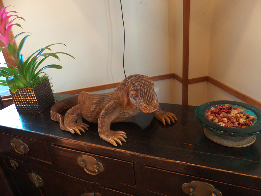 a detailed lizard sculpture on sideboard in lobbly at Dinah's Garden Hotel