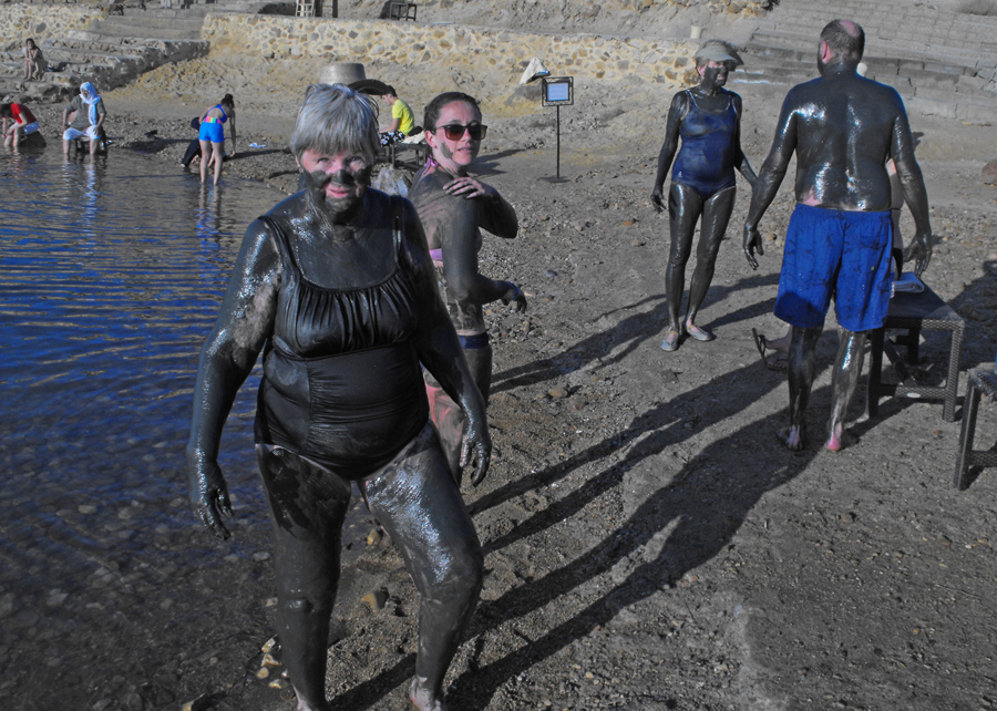 People covered with mud on the banks of  Dead sea