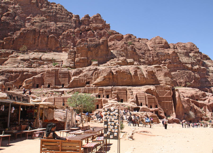 Vendors in foreground with Petra tombs in background