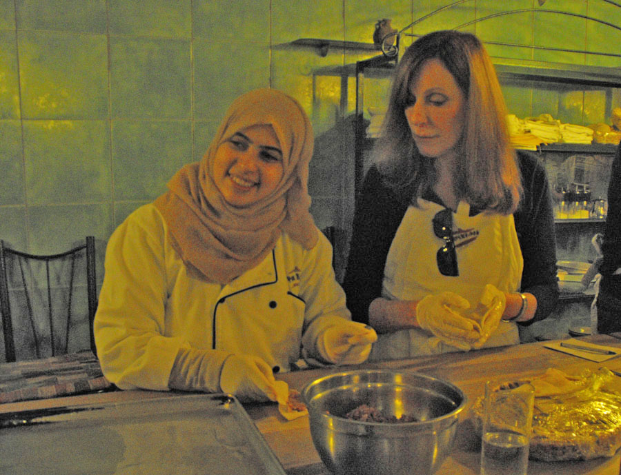 Muslim and American woman at table preparting food at Petra Kitchen
