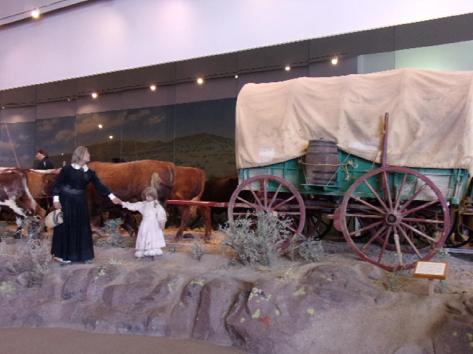 A covered wagom wit woman and child in life size diorama depicting life on the Oregon Trail inside the Interpretive Center