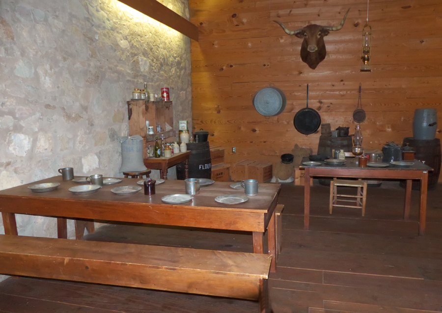 Typical enlisted men;s mess hall at Fort Concho including utensila sn cookware on tables
