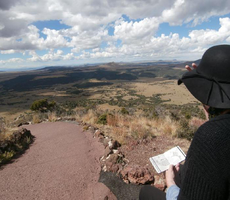 Woman holding her hat seated on the rim of Capulin Volcano