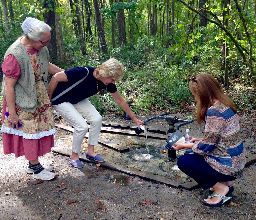 Three women getting a cup of water from God's Acre Healing Springs