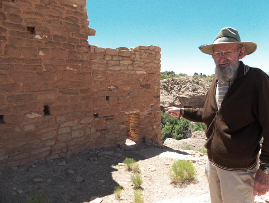 Man pointing to back wall at Cajon Ruins in Hovenweep