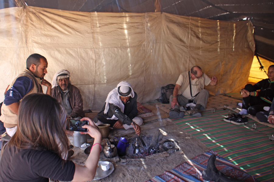 Group of people in Bedouin tents as elder makes coffee at Wadi Feynan