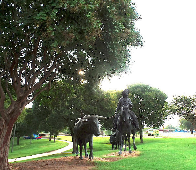 Sculpture of cowboyu and longhorns on Waco riverwalk next to Brazos River
