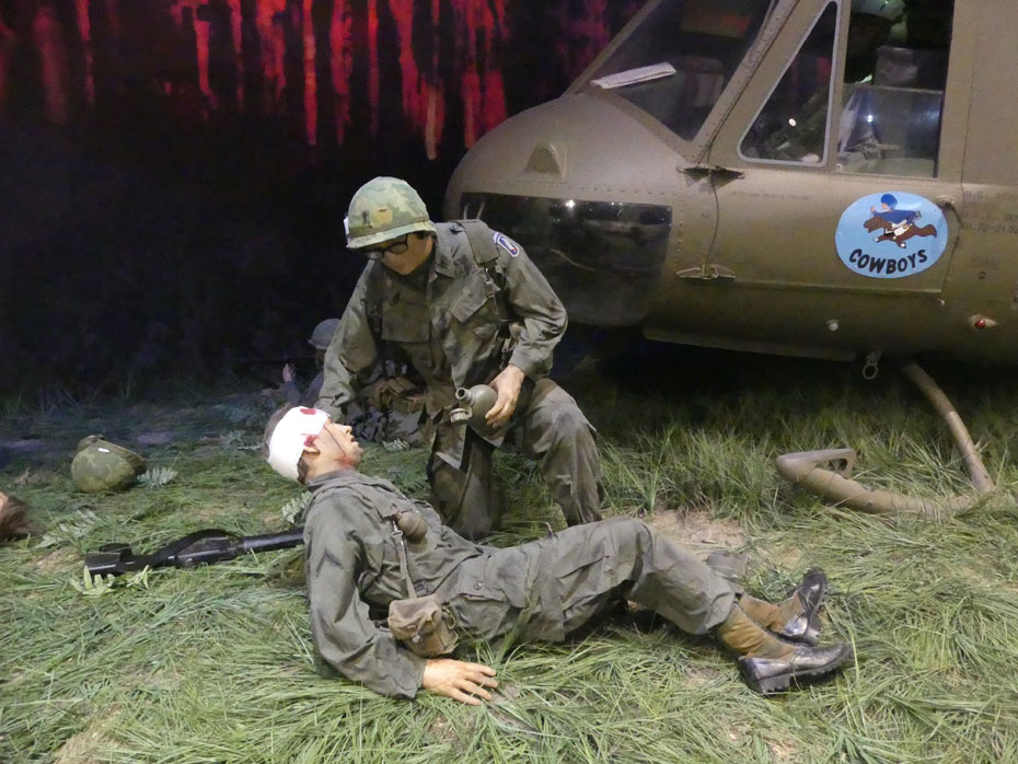 Medic aids wounded soldier exhibit with Cowboy helicopter in background