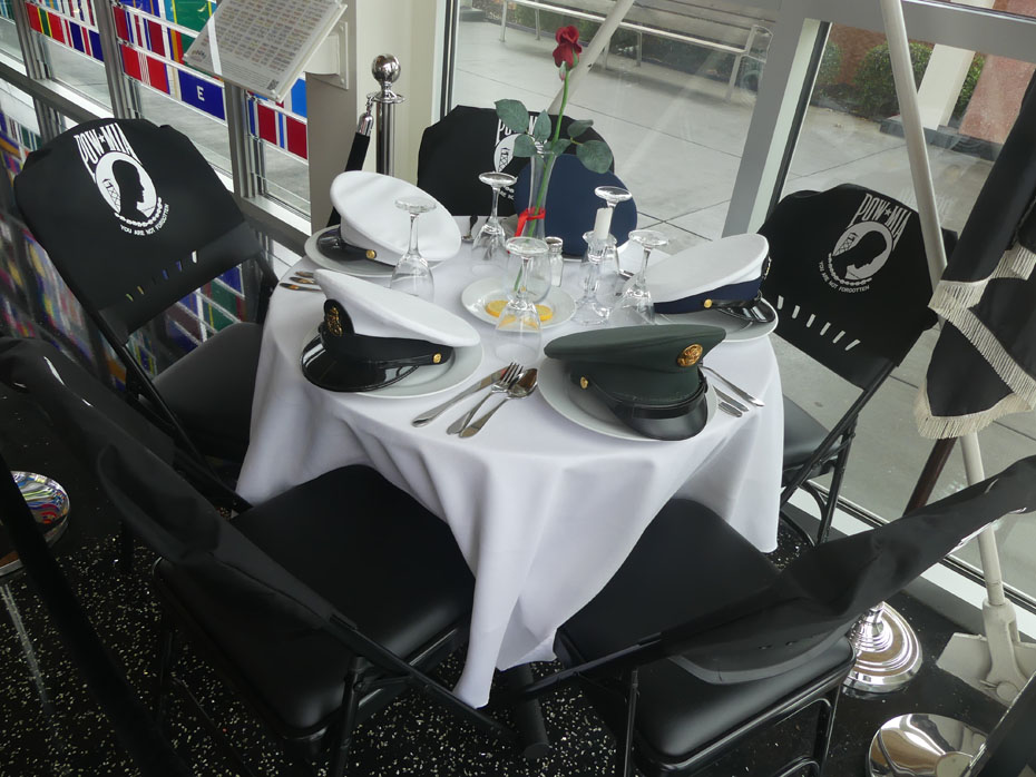 round table set wiht five places displaying hats from each of the Americna services wth MIAs called the Missing Man Table