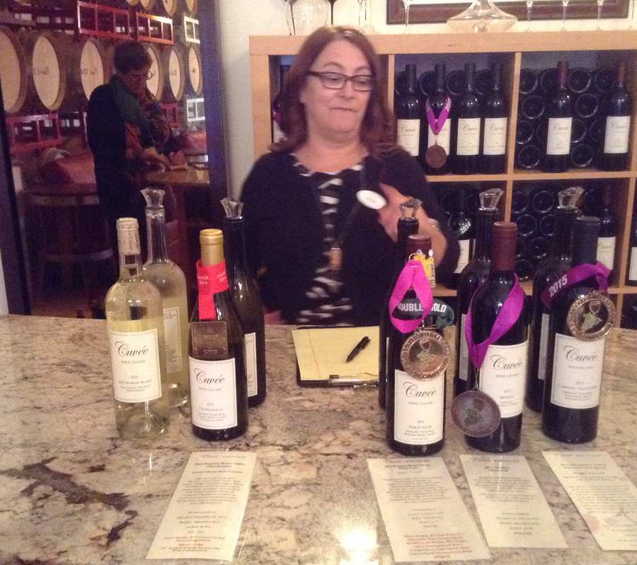 woman stanidnb behind table with wine from Cuvee Wine Cellar