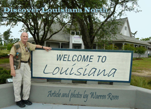 Welcome sign with author in fornt of Louisiana CVB office